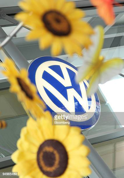 Volkswagen logo is seen between sunflowers at a dealership in Nuremberg Germany on Wednesday July 22 2009 Volkswagen AG and Porsche SE may delay an...