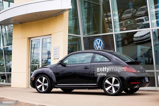 volkswagen new beetle in front of car dealership - volkswagen beetle stock photos and pictures