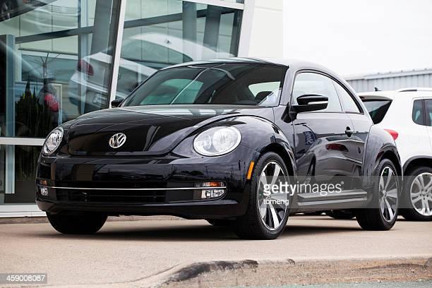 Volkswagen New Beetle in Front of Car Dealership