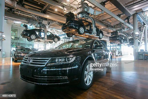 Volkswagen Phaeton automobiles move along elevated conveyors inside the Volkswagen AG factory in Dresden Germany on Thursday April 9 2015 German...