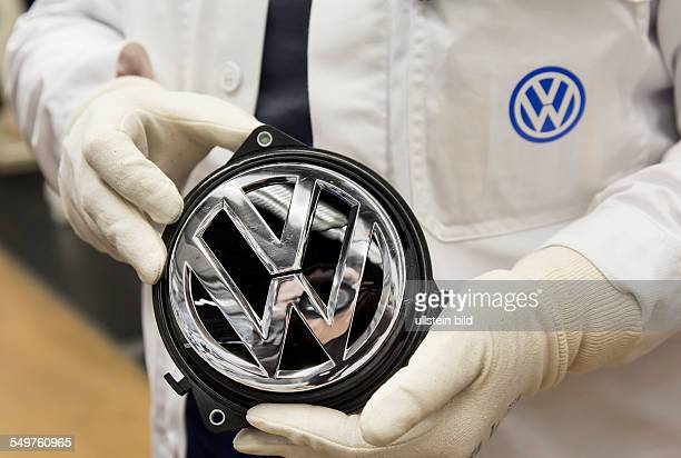 Volkswagen production site worker holding VW emblem in the hands Germany Europe