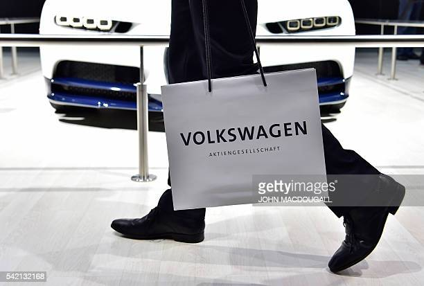 A Volkswagen shareholder walks past a car on display during German carmaker Volkswagen shareholders' annual general meeting on June 22 2016 in...