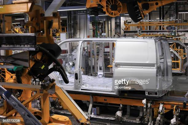 A Volkswagen Transporter T6 panel van body stands on the underbody shield robotic assembly line inside the Volkswagen AG factory in Hanover Germany...