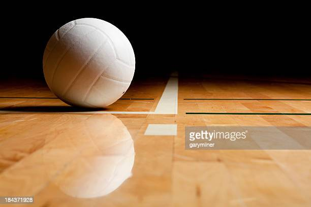 A volleyball and reflection on a wooden floor