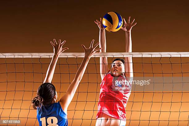 Volleyball block action on the net.