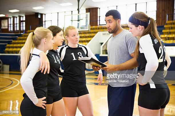 volleyball coach talking to female players - damen volleyball stock-fotos und bilder