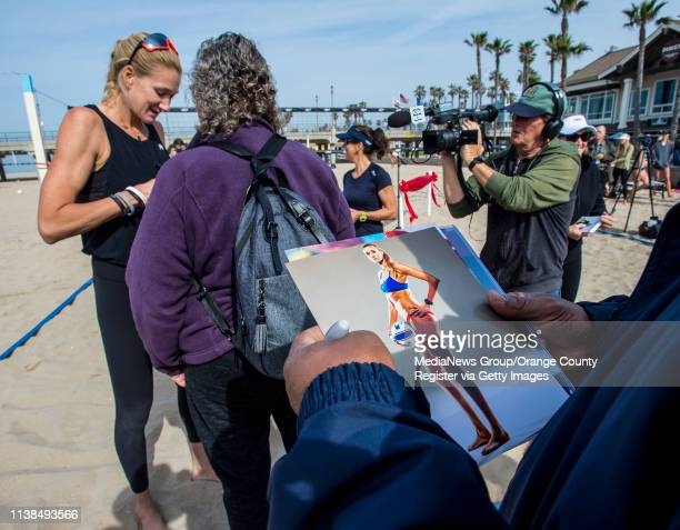 Volleyball fans wait in line on the beach near the Huntington Beach Pier on Tuesday morning March 26 in Huntington Beach as Olympic gold medalist...