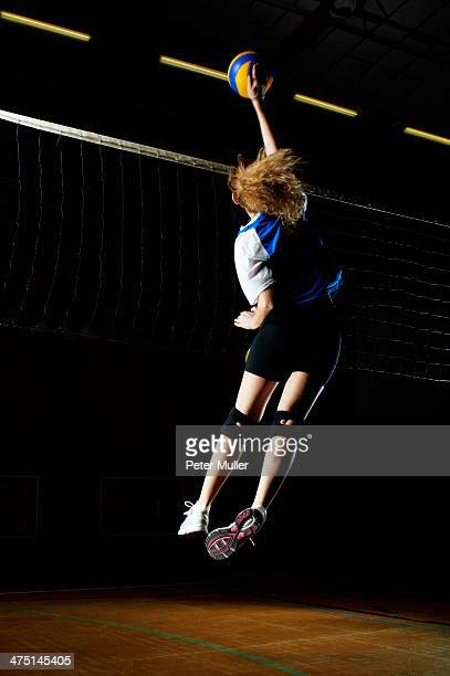 Volleyball player jumping for ball by net