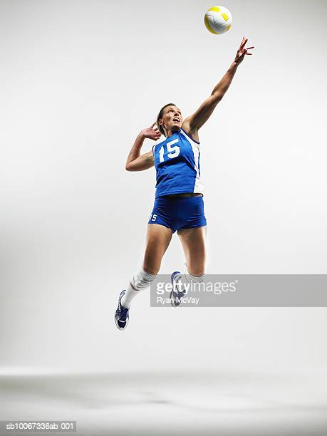 Volleyball player jumping to hit ball (studio shot)