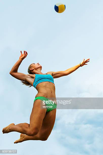 volleyball player serving in mid-air - beachvolleybal stockfoto's en -beelden
