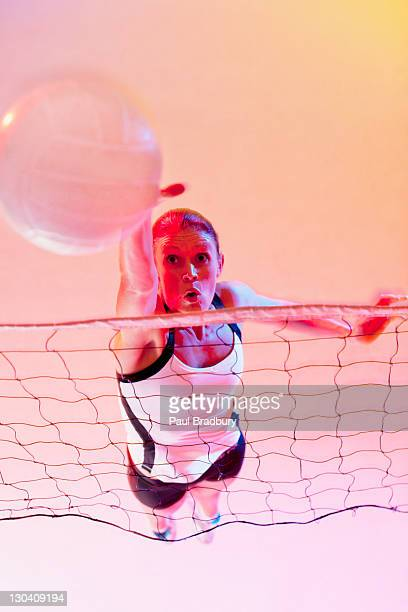 volleyball player spiking ball over net - spiking stock photos and pictures