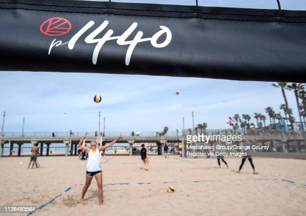 Volleyball players practice on the beach next to the Huntington Beach Pier on Tuesday morning March 26 in Huntington Beach following a ceremony in...