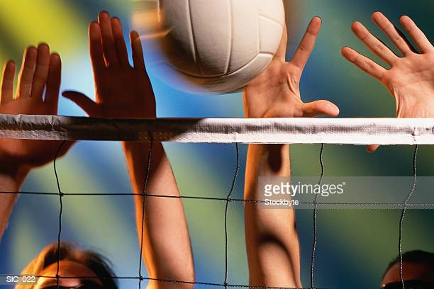 Volleyball players reaching for ball