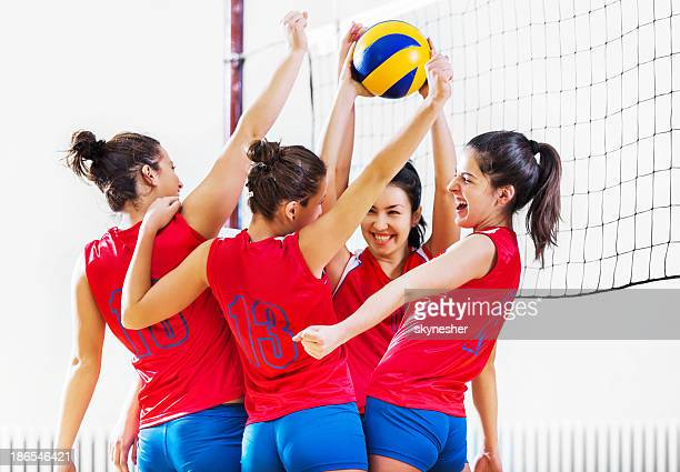 Volleyball team celebrating after winning.