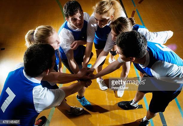 Volleyball team having team huddle