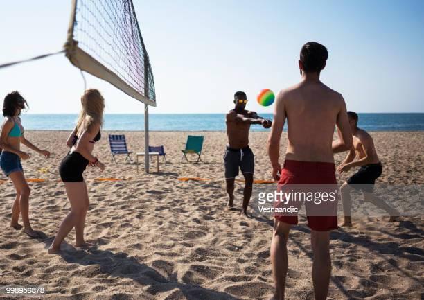 volleyball mit freunden am strand - strand volleyball der männer stock-fotos und bilder