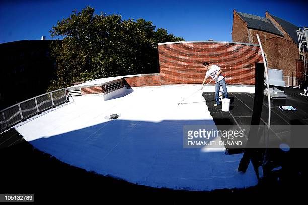 Volounteers paint a school�s roof with a special white paint that reflects nearly 80% of sunlight helping to keep the roof much cooler while reducing...