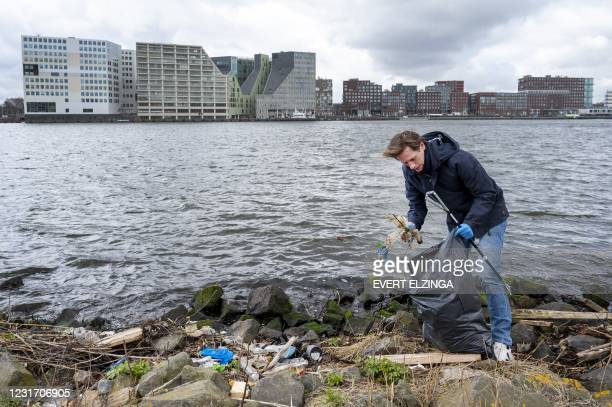 Volt party leader Laurens Dassen cleans up waste from the river IJ during his campaign for the parliamentary elections at EYE Amsterdam, on March 14,...