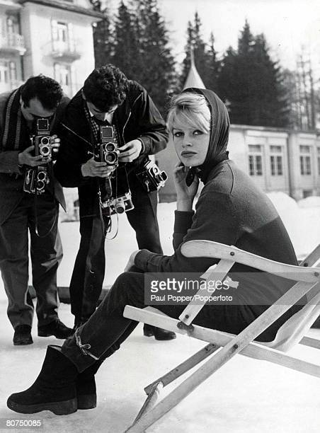Volume 2 Page 100 Picture 7 French film star Brigitte Bardot sits in chair outside at a ski resort whilst 2 photographers take her picture circa 1961