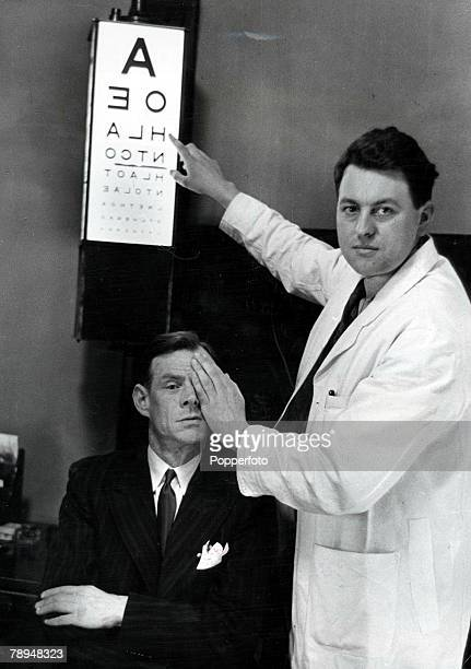 Volume 2, Page 120, Picture 8, London, England An ophthalmologist holds his hand up to cover a patient+s eye during an eye test after he underwent a...