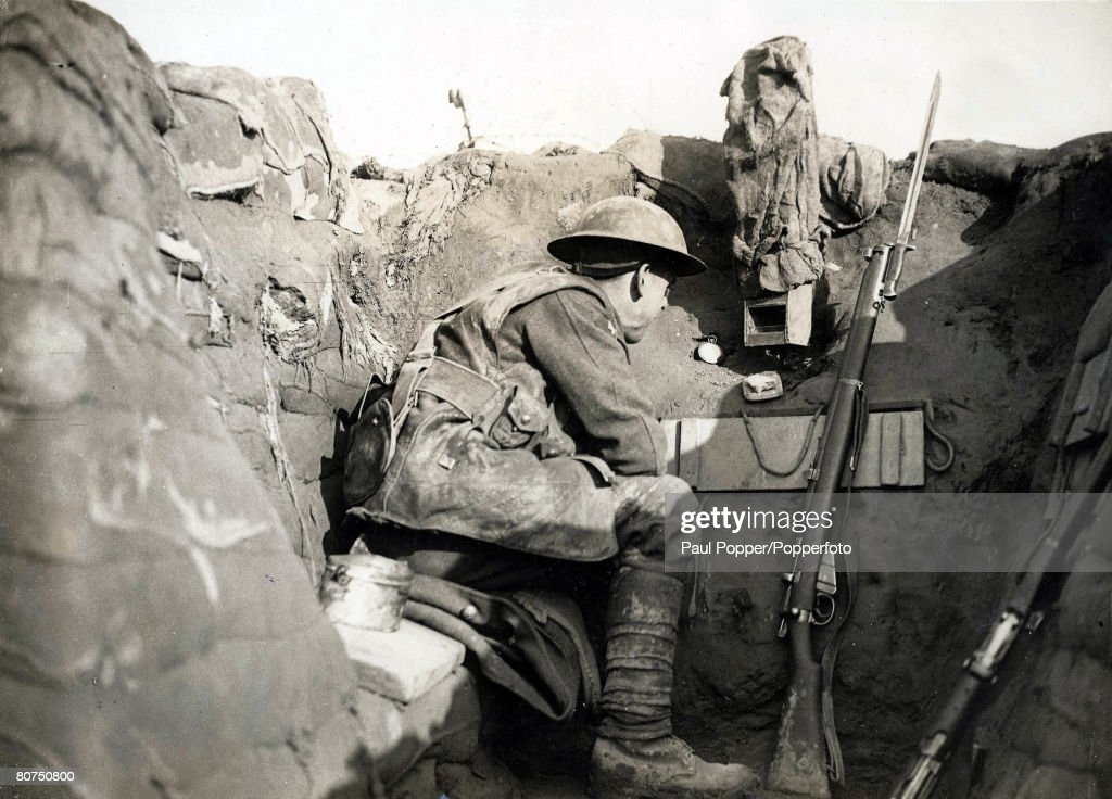 Volume 2, Page 124, Picture 2, World War One, 1914 - 1918, Western Front, France, A British Soldier looking out over their trenches towards enemy positions using a camouflaged periscope