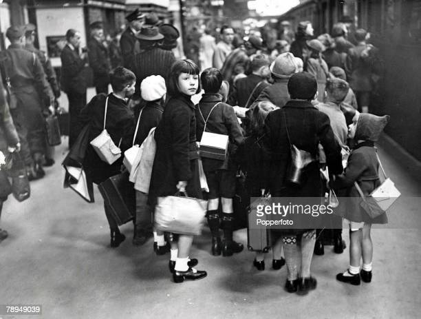 Volume 2 Page 126 Picture 1 World War Two London England A group of evacuee children carrying their belongings in suitcases and bags as they stand at...