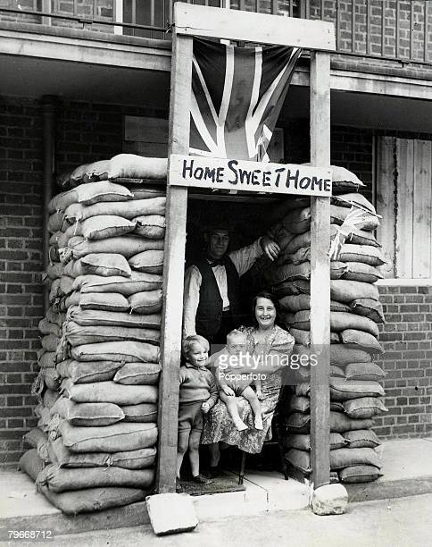 Volume 2 Page 127 Picture 8 World War Two England A family smiling at the camera as they sit in their air raid shelter made by sandbags with a sign...