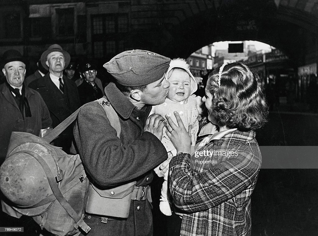 Volume 2. Page 128. Picture 7. World War Two. London, England. 1940+s. A soldier kisses his baby, held in the arms of his wife, as he says goodbye to his family at the rail station before going away to fight in the war. : News Photo