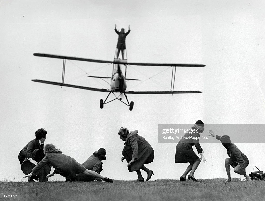 Volume 2, Page 130, Picture 5, Wycombe Air Park, England, 23rd May, 1968, 28-year-old BEA air stewardess Elaine Mitchael wingwalking on top of a Tiger Moth bi-plane while others duck down on the ground as the plane comes in to land.