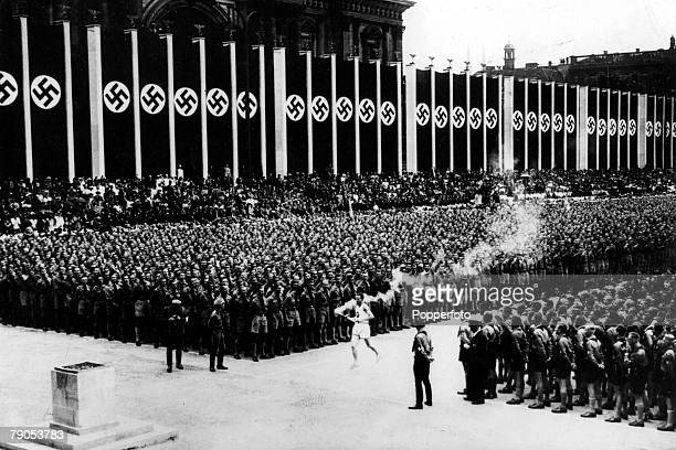 Volume 2 Page 23 Picture 3 1936 Olympic Games Berlin Germany The Olympic flame arrives at the Opening Ceremony to a packed stadium covered with...