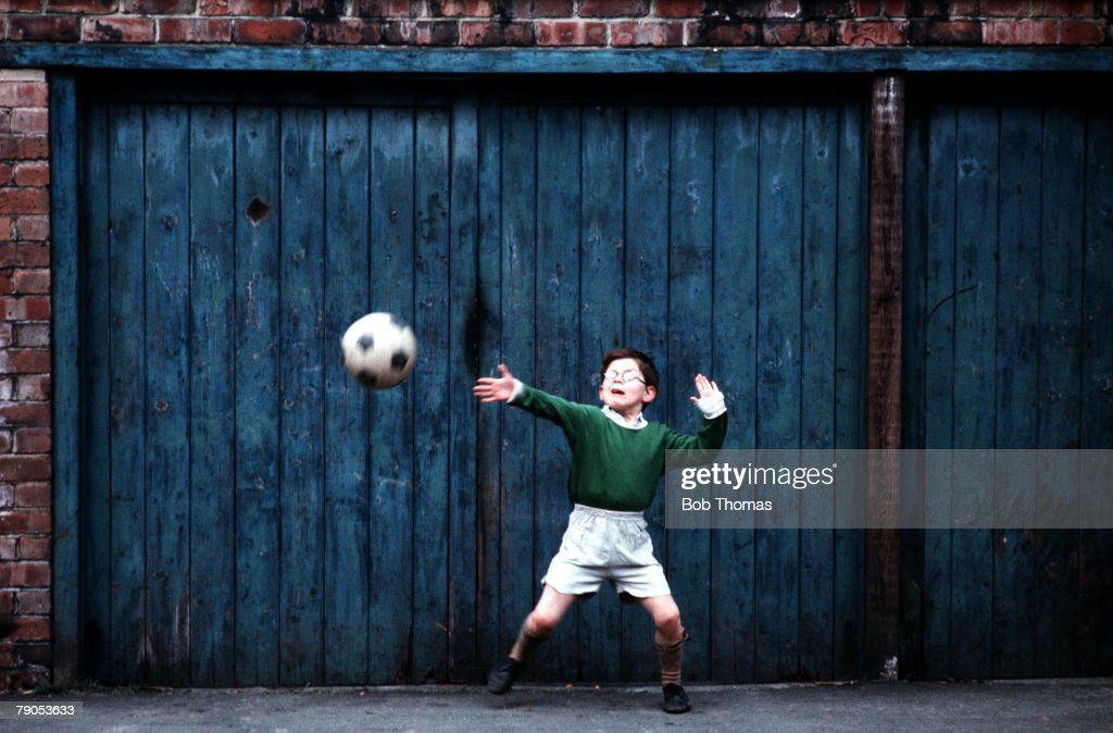 Volume 2, Page 32, Picture,4, 10237021, A young Backstreet goalie, palying a game of football, using the garage door as a goal in the streets of Manchester, Circa: 1970