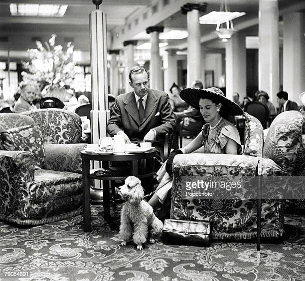 48 Picture 2 London England A model sitting on an armchair with a 100 guinea poodle dog by her side in Grosvenor House lobby after enjoying tea