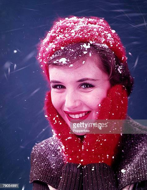 Volume 2 Page 51 Picture 7 A woman protects her cheeks from the cold snow as she wears red mittens and hat