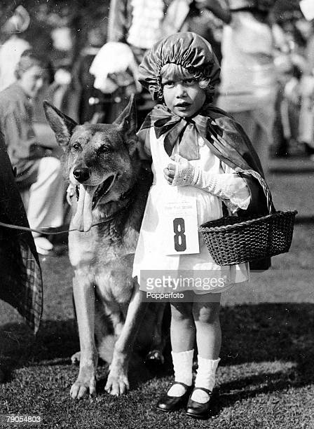 Volume 2 Page 61 Pic 4 A little girl is dressed as Little Red Riding Hood with an Alsatian as the Wolf