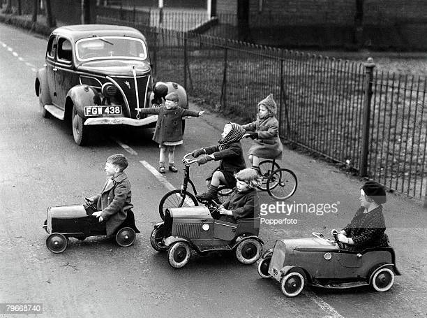 Volume 2 Page 63 Picture 9 Group of children riding an assortment of pedal cars bicycles and tricycles cross a road infront of a real car during...