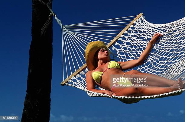 Volume 2 Page 94 Picture 3 Girl in yellow bikini and a hat lying on a large hammock