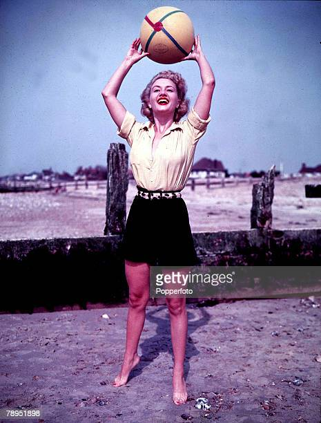 Volume 2 Page Picture A lady on the beach wearing black shorts and yellow shirt holding a beachball above her head circa 1950s