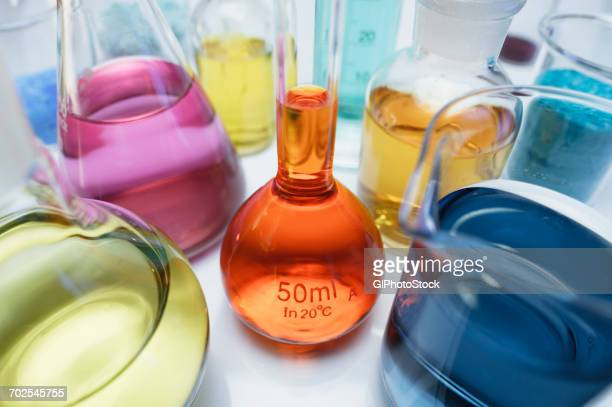 Volumetric flask containing solution of potassium dichromate (VI) (K2Cr2O7) and other flasks of transition metal salts, dry chemicals and solutions. Compounds with transition metals are often colored
