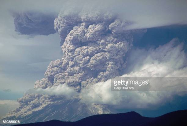 Voluminous plumes of volcanic ash and rock rises from Mount Saint Helens on May 18 with Mount Rainier across the Washington landscape.
