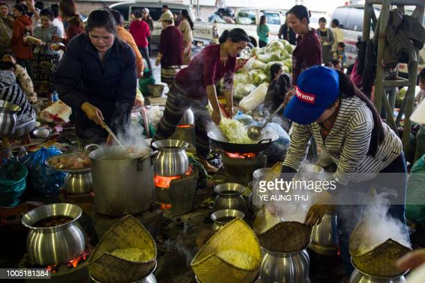Volumteers prepare meals for displaced residents seeking shelter in Paksong town Champasak province following massive floodings from the collapsed...