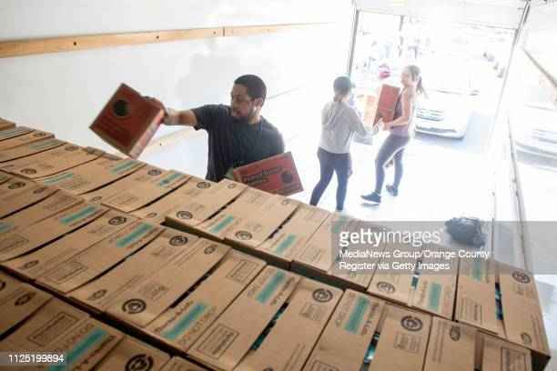 Volunteer Aaron Thornton of Fullerton helps stack Peanut Butter Patties in the back of a moving truck part of a 570 case order for FullertonLa Habra...