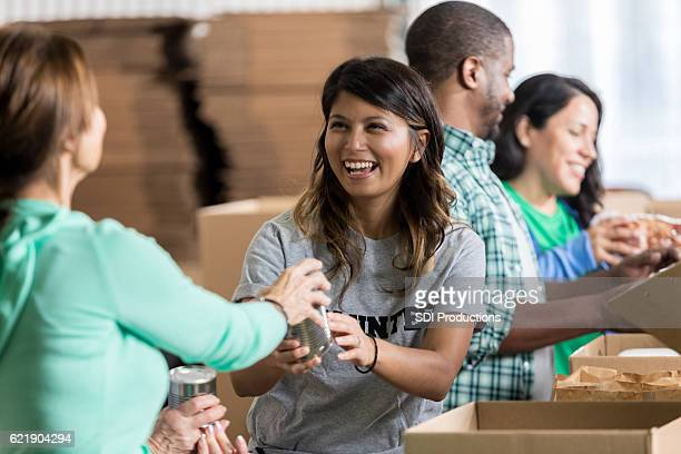 volunteer accepts canned food donation at food drive - humanitarian aid stock pictures, royalty-free photos & images