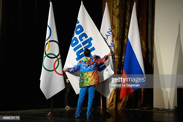 Volunteer adjusts a flag on stage during the opening of the IOC session on February 4 2014 in Sochi Russia