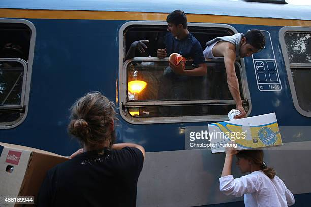 A volunteer aid worker gives out food to hundreds of migrants packed on a train at Roszke train station destined for the Austrian border after the...