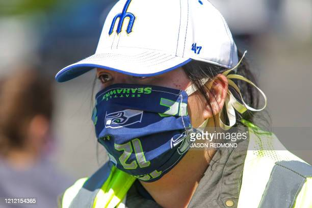 Volunteer Aileen Angeles wears a Seattle Mariners hat and Seattle Seahawks mask as she helps hand out potatoes donated by Washington potato farmers...