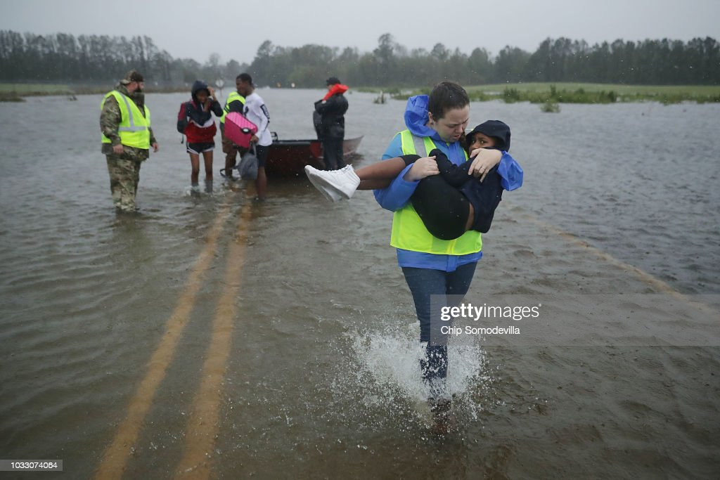 Volunteer Amber Hersel from the Civilian Crisis Response Team helps rescue 7-year-old Keiyana Cromartie and her family from their flooded home September 14, 2018 in James City, United States. Hurricane Florence made landfall in North Carolina as a Category 1 storm and flooding from the heavy rain is forcing hundreds of people to call for emergency rescues in the area around New Bern, North Carolina, which sits at the confluence of the Nueces and Trent rivers.