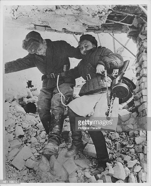 Volunteer army nurse helps a wounded Russian soldier during the Battle of Stalingrad in World War Two, Russia, circa 1942-1943.