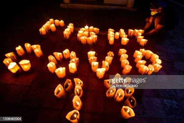 "Volunteer arranges lit candles in a formation to read ""Fight Covid-19"" during the Earth Hour environmental campaign near a catholic church in..."