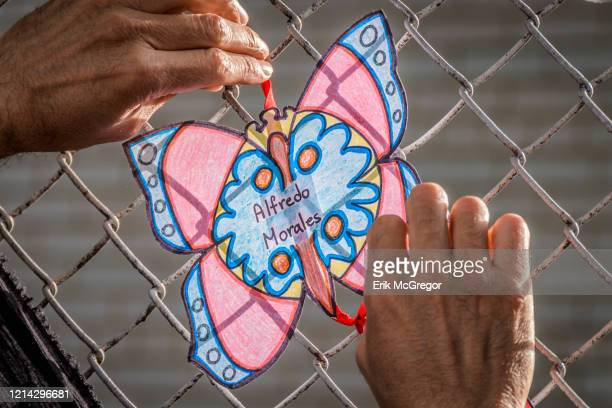 Volunteer artist tying a butterfly cutout with the names of COVID-19 fatalities. Artists and volunteer organizers across New York City put up...