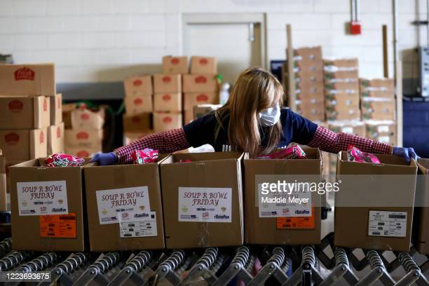 A volunteer assembles boxes of food for families as part of the SoupR Bowl at Gillette Stadium on May 08 2020 in Foxborough Massachusetts The...